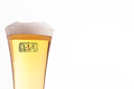 glass half full: weighing scales against half glass full of glass and foam