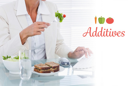 additives: The word additives against businesswoman using computer while eating salad at desk Stock Photo