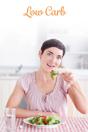 carb: The word low carb against cheerful brunette woman eating salad Stock Photo