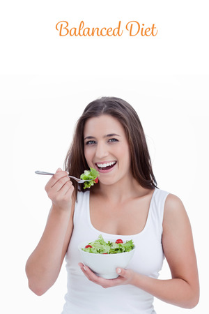 balanced diet: The word balanced diet against smiling young woman eating a salad