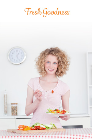 goodness: The word fresh goodness against attractive blonde woman eating some vegetables in the kitchen