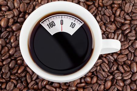 weighing scales: weighing scales against cup of coffee Stock Photo