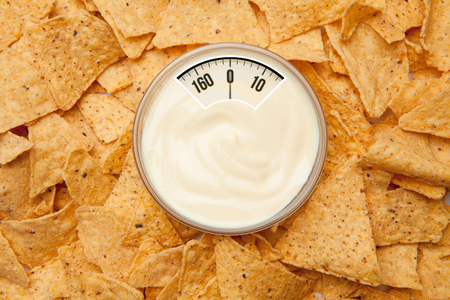 weighing scales: weighing scales against bowl of dip placed among nachos