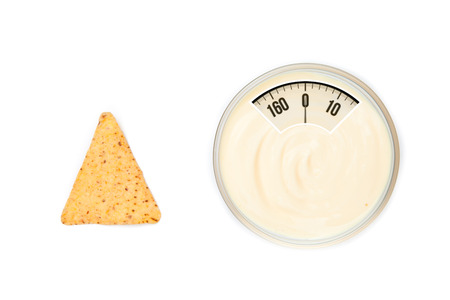 nacho: weighing scales against a bowl of dip and a nacho placed side by side