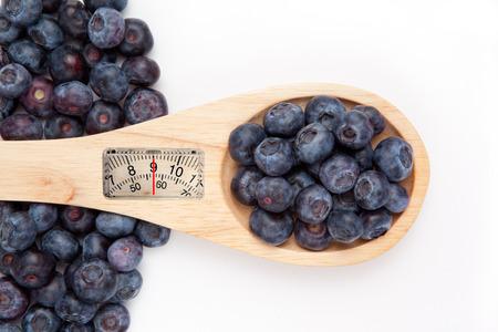 weighing scales: bilance contro cucchiaio di legno con blueberrry Archivio Fotografico