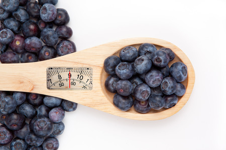 weighing scales: weighing scales against wooden spoon with blueberrry Stock Photo