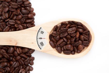 weighing scales: bilance contro cucchiaio di legno con i semi del caff�