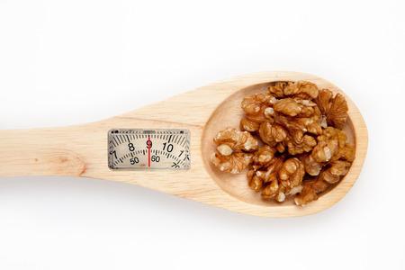 weighing scales: bilance contro cucchiaio di legno con le noci Archivio Fotografico