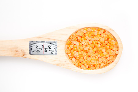 weighing scales: weighing scales against wooden spoon with lentils