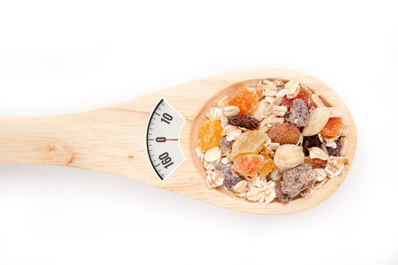 weighing scales: weighing scales against wooden spoon with muesli
