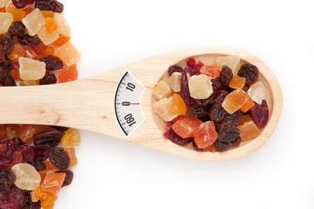 weighing scales: weighing scales against wooden spoon with dried fruit
