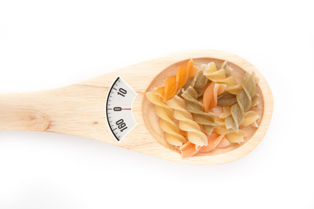 weighing scales: weighing scales against wooden spoon with pasta Stock Photo