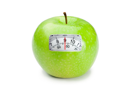 weighing scales: weighing scales against green apple Stock Photo