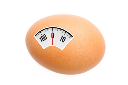 weighing scales: weighing scales against egg Stock Photo