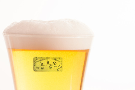 weighing scales: weighing scales against top of glass full of beer and foam Stock Photo