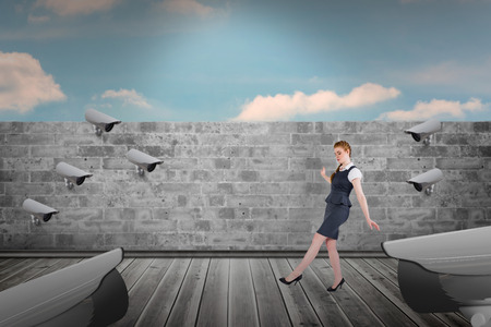 balancing act: Businesswoman doing a balancing act against blue sky over brick wall