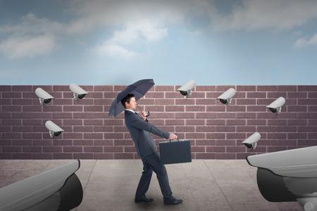 sheltering: Businessman sheltering under black umbrella against blue sky over a brick wall