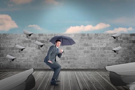 sheltering: Businessman sheltering under black umbrella against blue sky over brick wall