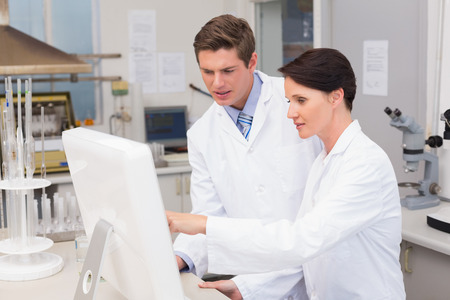 attentively: Scientists looking attentively at computer in laboratory Stock Photo