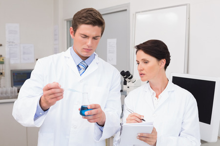 attentively: Scientists examining attentively pipette with blue fluid in laboratory
