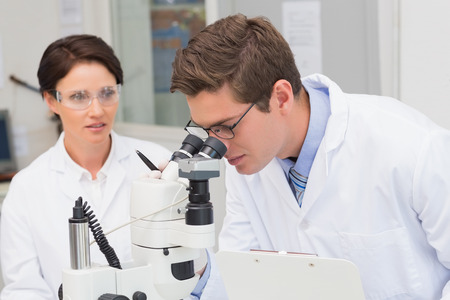 attentively: Scientists looking attentively in microscope in laboratory