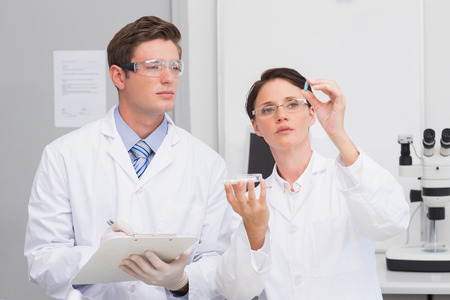 attentively: Scientists looking attentively at pill in laboratory Stock Photo