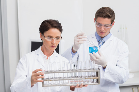attentively: Scientists looking attentively at test tubes in laboratory