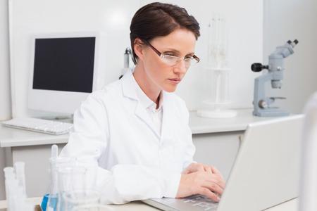 biochemist: Scientist working attentively with laptop in laboratory