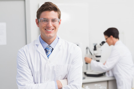 Scientist smiling at camera arms crossed and another working with microscope in laboratory