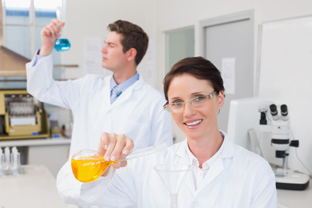 attentively: Scientists working attentively together with beakers in laboratory