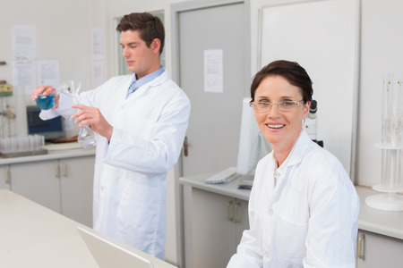 attentively: Scientist working attentively with laptop and another with beaker in laboratory