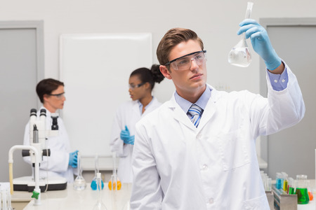 scientist woman: Scientist looking at white precipitate while colleagues talking together in the laboratory