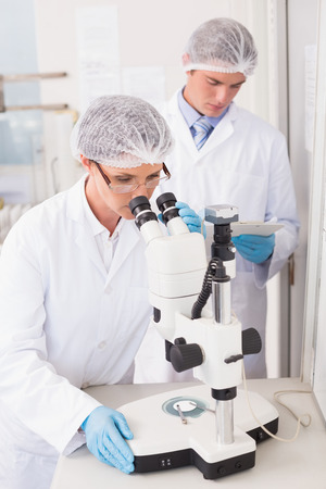 attentively: Scientists working attentively with microscope in laboratory