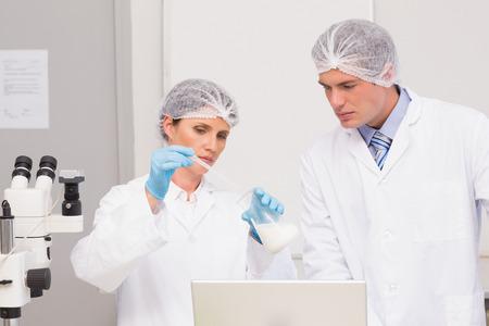 beaker: Los cient�ficos que trabajan con atenci�n con el cubilete en el laboratorio