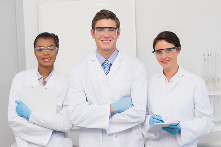 scientist man: Scientists smiling and looking at camera in laboratory