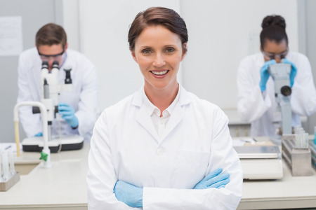 Happy scientist smiling at camera with arms crossed in the laboratory