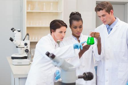 precipitate: Scientists looking at green precipitate in the laboratory