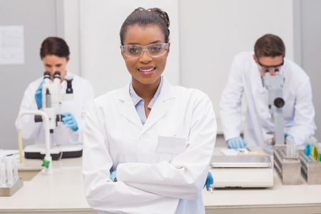 protective glasses: Happy scientist smiling at camera with protective glasses in the laboratory