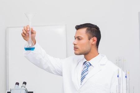precipitate: Focus scientist looking at blue precipitate in the laboratory