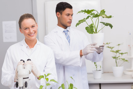 Scientist smiling at camera while colleague looking at plant in the laboratory photo