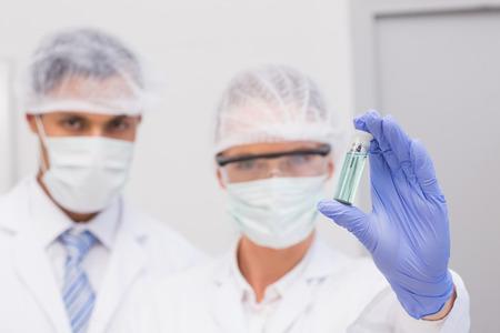 precipitate: Scientists examining green precipitate in tube in the laboratory
