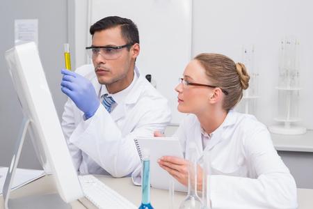 precipitate: Scientists examining yellow precipitate in tube in the laboratory