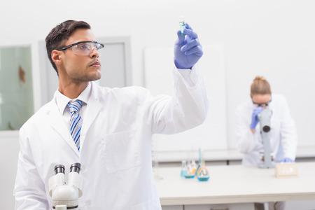 precipitate: Scientist examining blue precipitate in tube in the laboratory Stock Photo