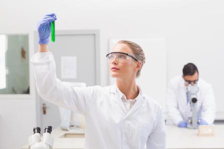 precipitate: Scientist examining green precipitate in tube in the laboratory