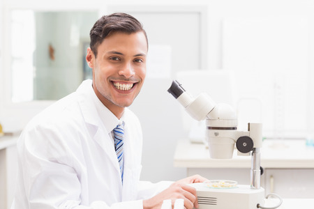 observing: Smiling scientist observing petri dish with microscope in laboratory