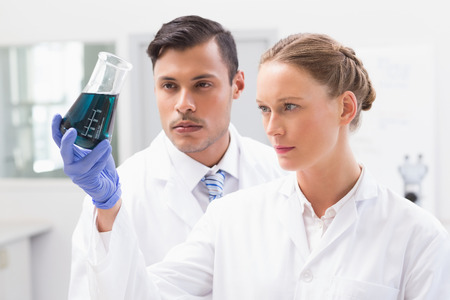 concentrated: Concentrated scientists holding beaker with fluid in laboratory Stock Photo