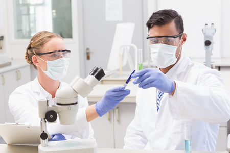 concentrated: Concentrated scientists looking at beaker in laboratory Stock Photo