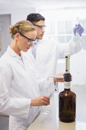attentively: Scientists working attentively with beaker in laboratory