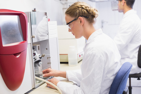 concentrated: Concentrated scientists working with medical machine in laboratory