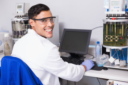 biochemist: Smiling scientist working with computer in laboratory Stock Photo